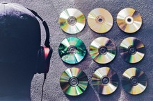 Rear View Of Man Wearing Headphones By Compact Discs On Wall