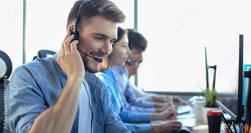 Portrait of call center worker accompanied by his team Canvas Print