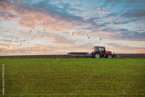 farmer plowing his fields at sunset Fototapeta