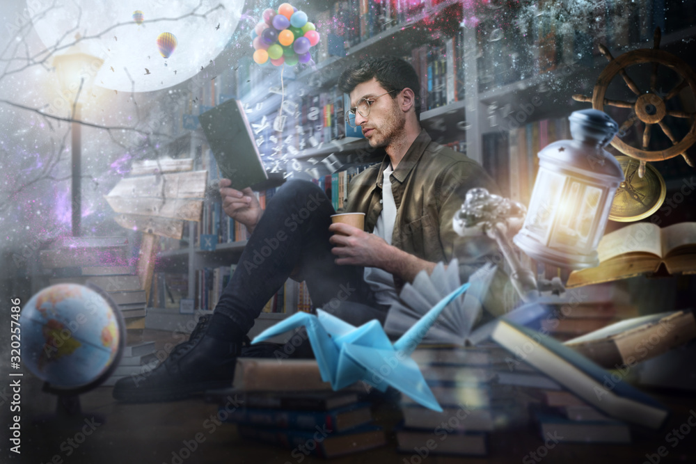 Fototapeta Boy reads a book at night in a library. Concept of fantasy, imagination and creativity