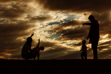 Silhouette Family Pointing Fingers On Field Against Orange Clouds In Sky