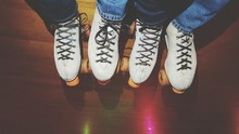 Low Section Of People In Roller Skate Standing On Hardwood Floor