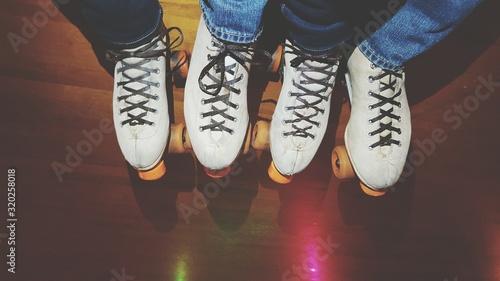 Obraz na plátně Low Section Of People In Roller Skate Standing On Hardwood Floor