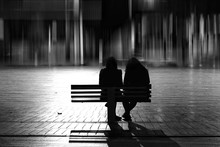 Rear View Of Silhouette Female Friends Sitting On Bench In City At Night