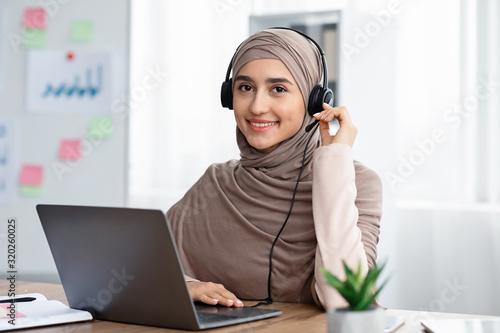 Photo Beautiful arabic woman in hijab wearing headset working in modern office