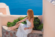 Santorini, Oia location. Spring - Summer season. Vacation and travelling time. Woman at sea, pretty nice view