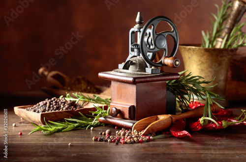 Fotomural Vintage pepper mill with kitchen utensils, spices and rosemary on a old wooden table