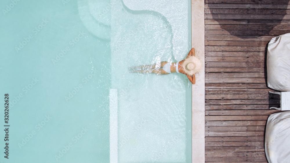 Fototapeta Woman in straw hat relaxing in clear pool water in hot sunny day on Bali villa