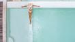 Leinwandbild Motiv Woman in straw hat relaxing in clear pool water in hot sunny day on Bali villa