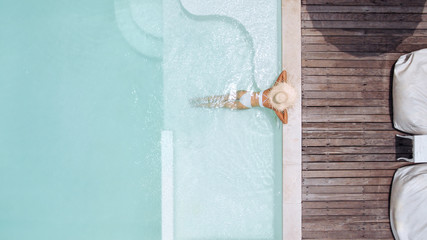 Woman in straw hat relaxing in clear pool water in hot sunny day on Bali villa