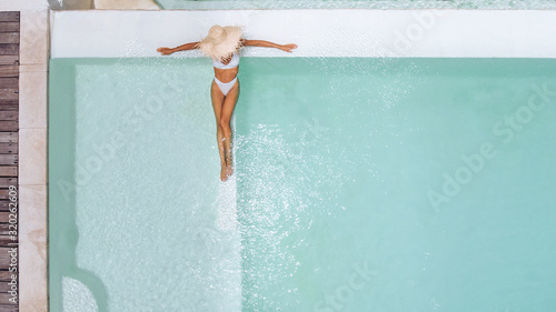 Woman in straw hat relaxing in clear pool water in hot sunny day on Bali villa Fototapeta
