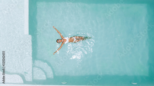 Fototapeta Woman relaxing in clear pool water in hot sunny day on Bali villa obraz
