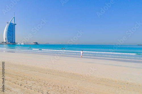 Burj Al Arab Hotel By Beach Against Clear Blue Sky Wallpaper Mural