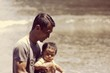 Leinwandbild Motiv Father With Son Walking By Lake