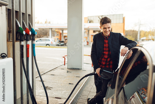 Photographie Man fuels vehicle on gas station, bottom view