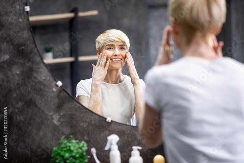 Fotografie, Tablou Lady Touching Face Skin Looking In Mirror In Bathroom