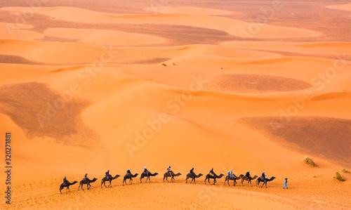Camel caravan with travelers among the sand dunes in beautiful Sahara Desert Wallpaper Mural