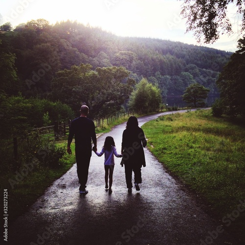 фотография Rear View Of Family Walking On Road