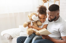 Cute Afro Family Father And Daughter Reading Book At Home