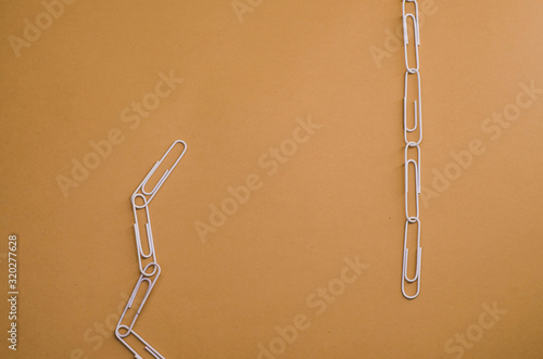 Fényképezés white paper clips connected with each other on a brown background