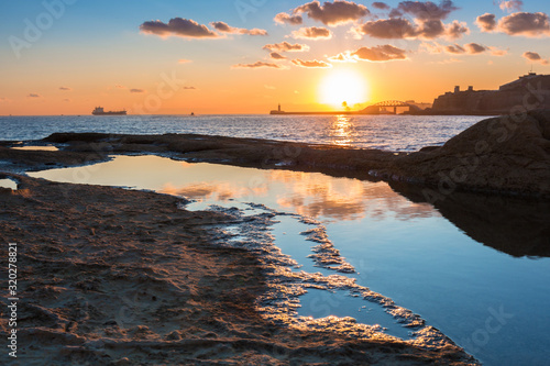 Fototapeta Rocky coastline of Malta and Mediterranean Sea at sunrise obraz