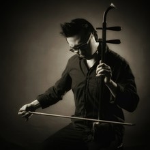 Young Man Playing Erhu Against Gray Background