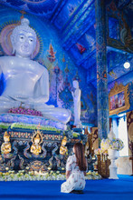 An Asian Woman Sitting In Front Of Buddha Statue At Wat Rong Suea Ten, The Blue Temple In Chiang Rai, Thailand