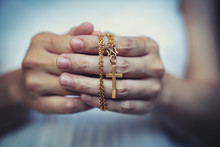 Woman Hands Praying Holding A Beads Rosary With Jesus Christ In The Cross Or Crucifix On Black Background.