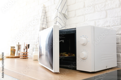 Photo Modern microwave oven in kitchen