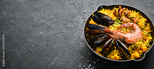 Fototapeta Seafood rice. Paella with mussels and shrimp. Top view. Free space for your text. obraz