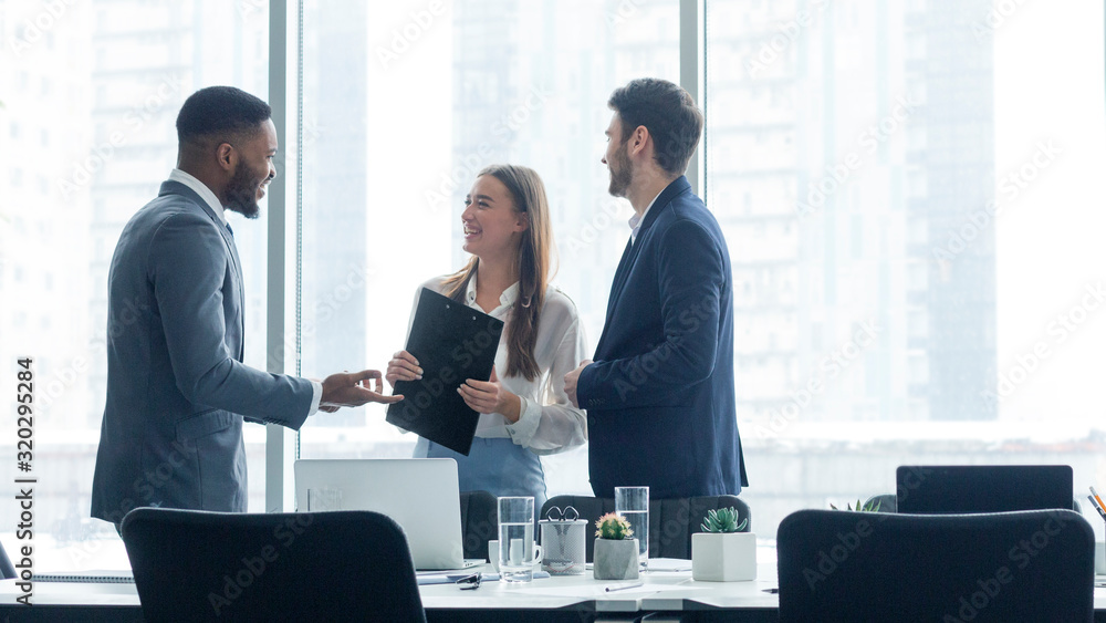 Fototapeta Happy business colleagues talking in front of office window