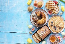 Easter Festive Dessert Table With Various Of Cakes, Waffles, Sweets And Strawberry. Blue Background. Overhead View