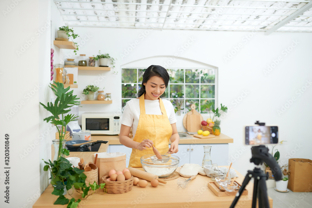 Fototapeta Pretty young asian female food blogger working on a new video and explaining how to cook a dish