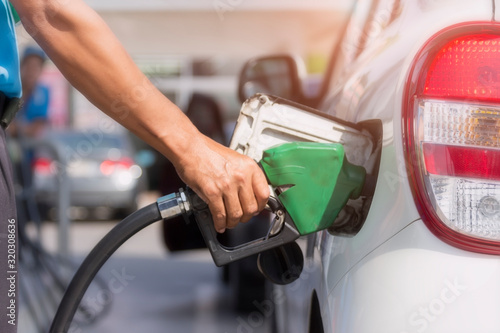 Fotomural Close up picture of hand is fueling petroleum to the white vehicle at the gas station