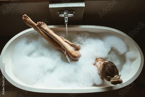 Valokuva Woman relaxing in foam bath with bubbles in dark bathroom by window