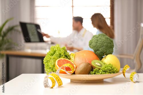 Żywiony konsultacyjny pacjent przy stołem w klinice, skupia się na talerzu z owoc, warzywami i pomiarową taśmą