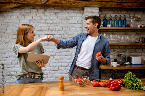 Fototapeta Lovely cheerful young couple cooking dinner together, looking recipe at digital tablet and having fun at rustic kitchen obraz