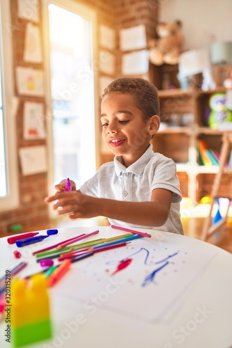Obraz Beautiful african american toddler drawing using paper and marker pen at kindergarten - fototapety do salonu