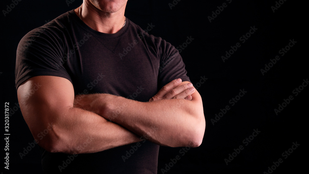 Fototapeta A man with strong arms. Male security guard in a black t-shirt. Strong man on a black background. Concept male security guard.