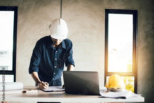 engineer working on blue print and search on laptop in construction site Billede på lærred