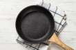Frying pan or skillet on white wooden table.