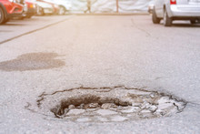 Pot Hole On Tarmac Road At City Street With Driving Car