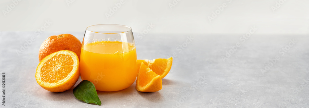 Fototapeta Fresh orange juice glass and oranges on light background