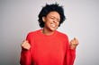 Leinwanddruck Bild - Young beautiful African American afro woman with curly hair wearing red casual sweater very happy and excited doing winner gesture with arms raised, smiling and screaming for success. Celebration