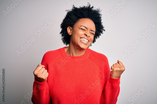 obraz PCV Young beautiful African American afro woman with curly hair wearing red casual sweater very happy and excited doing winner gesture with arms raised, smiling and screaming for success. Celebration