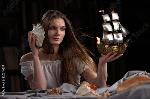 Photo A girl with a model of a sailboat, in the form of an allegory of the sea element