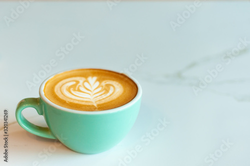 Fotografie, Obraz Fresh latte coffee in green cup on marble table with copy space.