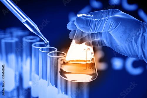 Obraz Flask in scientist hand with lab glassware background - fototapety do salonu
