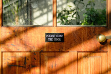 Polite Sign Seen Attached To An Interior, Glass House Wooden Door Informing People To Close The Door On Existing. The Glass House Is Used To Maintain Tropical Plants All Year Long