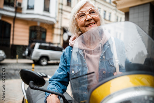 obraz dibond Cheerful aged woman riding motorcycle stock photo